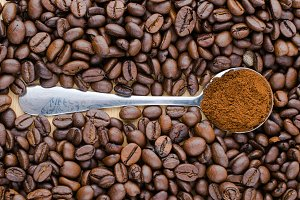 Metal spoon with ground coffee on table with coffee beans
