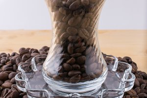 Glass cup on saucer with coffee beans on wooden table
