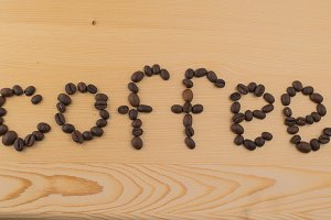 Sign coffee made of roasted beans on wooden table