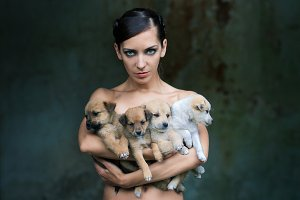 Beautiful woman holding four puppies