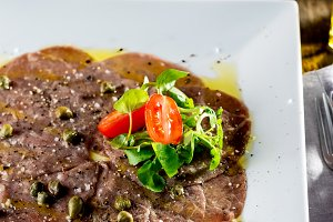 Beef carpaccio on white plate, wooden background. Close up