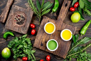 Oils, spices ahd herbs selection. Grape, olive and corn oils fresh herbs, lemons peppers. Top view