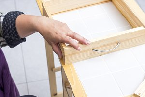 A carpenter builds a small white tab