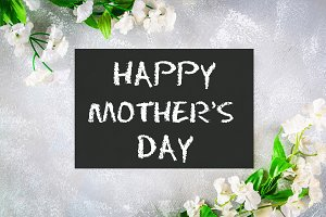 Happy mothers day. A chalkboard is surrounded by white flowers on a gray background.