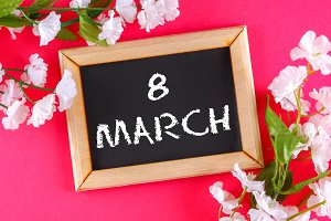 Chalkboard in a wooden frame surrounded by white flowers on a pink background. 8 march, women day.