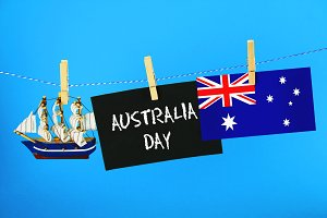 Chalkboard with the inscription: Happy day of Australia surrounded by shipwrights, a compass, a clock and an Australian flag on a blue background. 26 January.