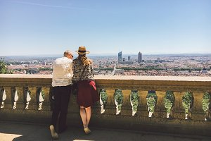 A pair of man and woman stand with their backs and look at the panoramic view from the high point to the city of Lyon in France in summer in sunny weather