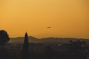 A low-flying plane and mountains are silhouetted at dusk.