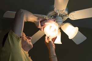 Senior caucasian man dusting lamp shade in ceiling fan and light