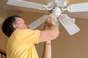 Senior caucasian man replacing bulb in ceiling fan and light