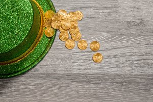 Pile of pure gold coins inside rim of green hat St Patricks Day