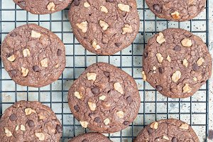 Homemade chocolate cookies with walnuts and chocolate chips on the cooling rack, top view, square format