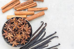 Different kinds of aromatic winter spices on a gray concrete background, top view, square