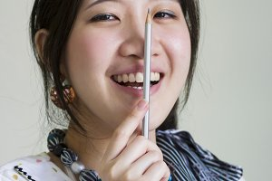 Happy asian woman holding pencil