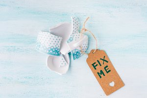 Broken cup relationship concept top view pastel background