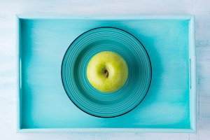 Green apple in ceramic dish on tray