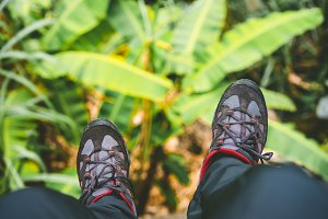Hanging feet with trakking footwear after long hike from the mountains on Santo Antao Island, Cape Verde. Banana leaves underneath.