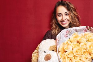 happy beautiful woman with a bouquet of roses and a toy dog