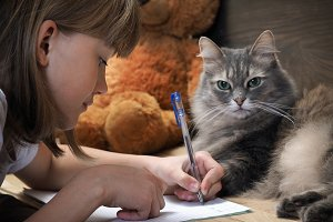 Girl doing homework, writing in a exercise book