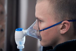 The man inhales the medication through the nebulizer