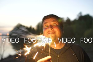 Portrait of young smiling man with sparkler celebrating at beach party