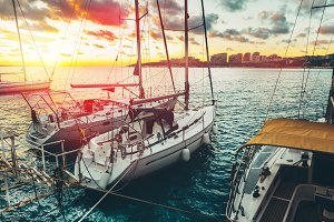 Beautiful white sailing yachts moored at the pier at sunset, scenic landscape