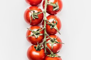 Red cherry tomatoes bunch on white