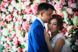 beautiful bride and groom on the background of a wall of flowers