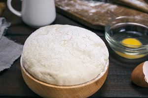 wheat yeast dough in a wooden bowl