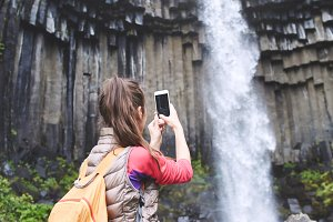 woman on background of Svartifoss waterfall surrounded by basalt columns in the south of Iceland