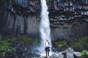 man on background of Svartifoss waterfall surrounded by basalt columns in the south of Iceland