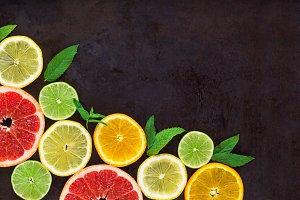 corner with slice of oranges, lemons, limes, grapefruit and mint pattern on black. Flat lay