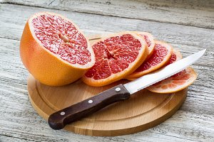 Sliced pieces of grapefruit with a knife. On white wooden background