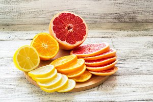 Sliced fresh lemons, grapefruits, oranges on a wooden cutting board with a knife