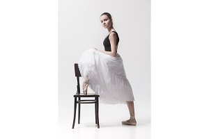 The teen ballerina in white pack posing near chair