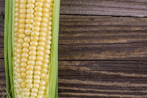 Fresh corn on cobs on rustic wooden table, closeup, top view, copy space
