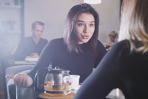 Black haired young woman with black hair drinking coffee and talking with girlfriend in the cafe