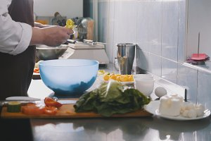 Male chef preparing salad in commercial kitchen - cleans the cabbage