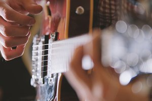 Male musician plays the guitar, hands close up, focus on the guitar fretboard