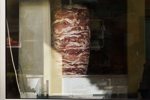 Photo of meat for shaurma cooking behind glass