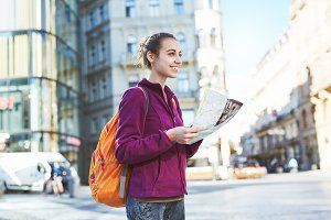 a woman tourist in the center of Prague with a map in the hands of