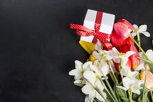 Bouquet daffodils and gift on the bl