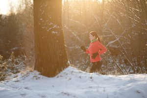 Photo of running sports girl on winter forest in morning