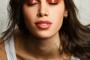 Image of beautiful brunette with closed eyes, bright make-up