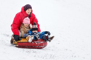 Picture of happy father, daughter and son on tubing in winter park