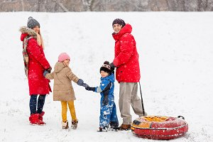 Photo from back of family walk with daughter and son, with tubing in winter