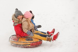 Image of mother with her daughter and son riding tubing in snowfall