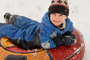 Image of boy on tubing in winter park