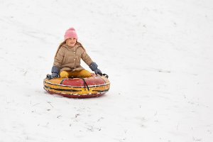 Photo of happy girl riding tubing in winter park