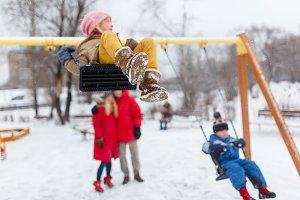 Image of happy girl and boy swinging in winter in park with parents